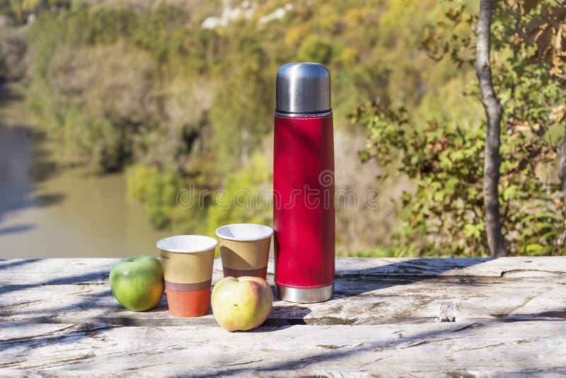 Meriende en el campo en la alta montaña con el termo, el café y manzanas rojos fotos de archivo libres de regalías