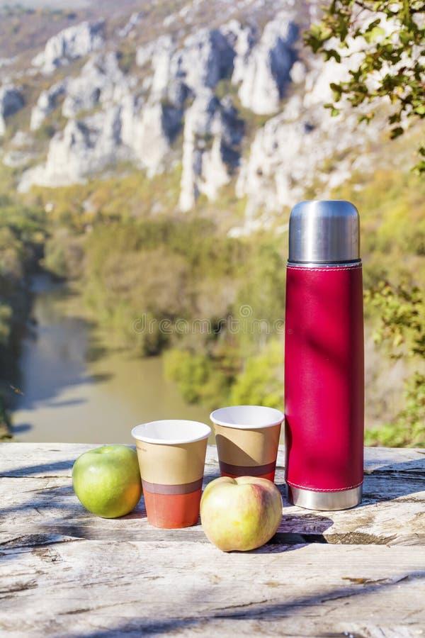 Meriende en el campo en la alta montaña con el termo, el café y manzanas rojos fotografía de archivo libre de regalías