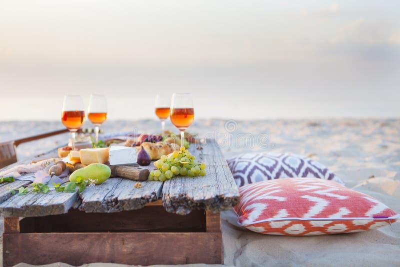 Meriende en el campo en la playa en la puesta del sol en estilo del boho, comida y beba concentrado imágenes de archivo libres de regalías