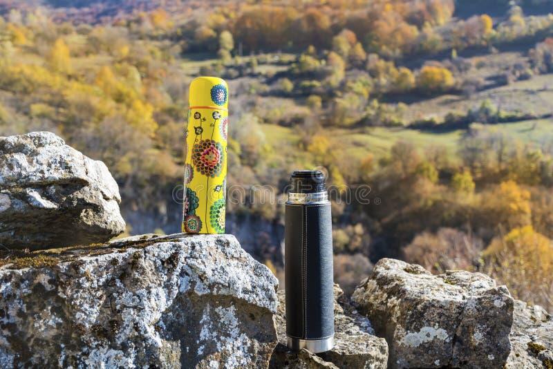 Meriende en el campo en la alta montaña del otoño con dos thermoses foto de archivo libre de regalías