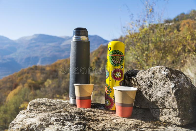 Meriende en el campo en la alta montaña del otoño con dos thermoses imagen de archivo