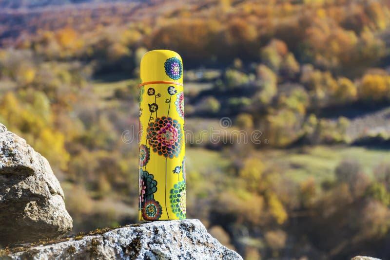 Meriende en el campo en la alta montaña del otoño con el termo amarillo fotografía de archivo