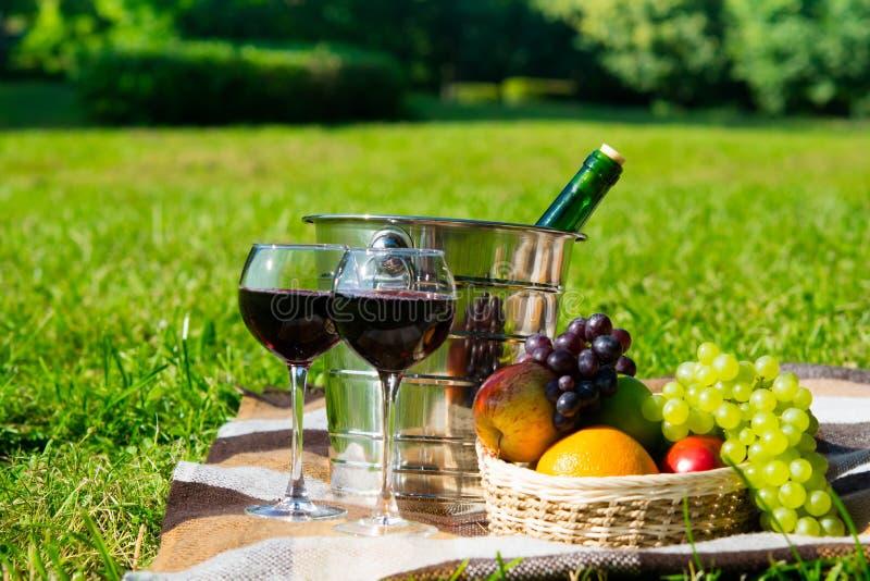 Meriende en el campo en la hierba con el vino enfriado en vidrios y una cesta de frutas frescas para dos fotos de archivo