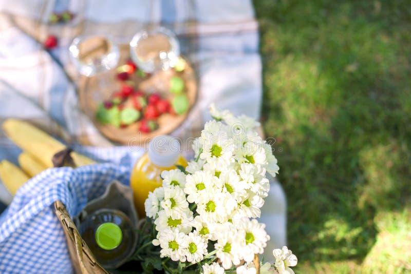 Meriende en el campo en el parque en la hierba verde, en un día de verano soleado Flores, cesta, vino en vidrios y una manta Copi fotos de archivo