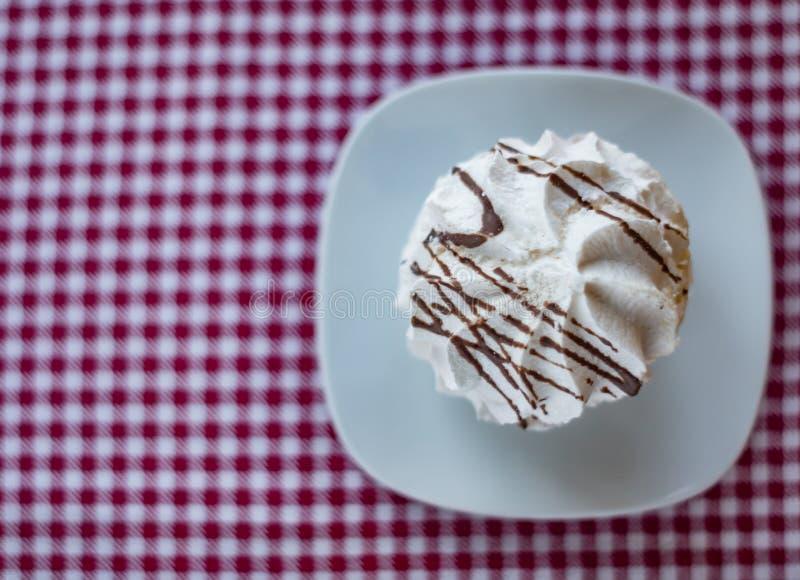 Meringa con le bande del cioccolato su un piatto immagini stock