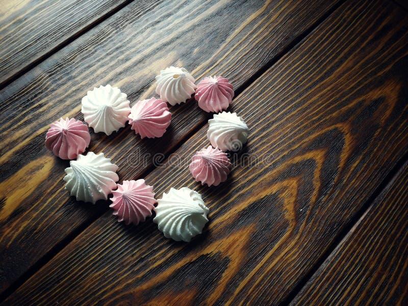Meringa rosa e bianca aerata su fondo di legno fotografie stock