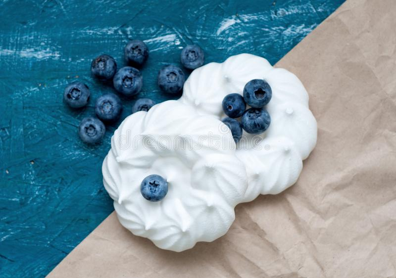 Meringekuchen mit Blaubeere auf dem blauen Hintergrund Alte Papierbeschaffenheit stockbilder