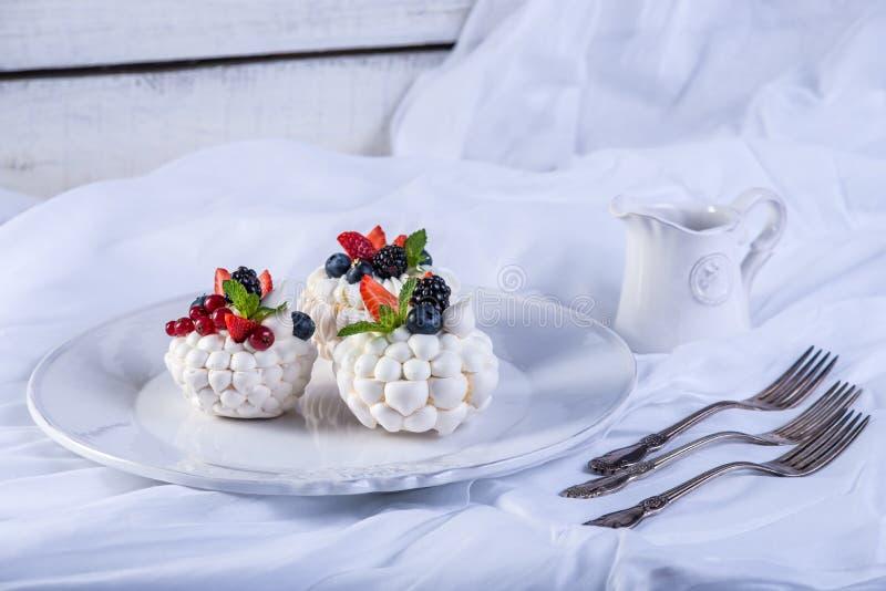 Meringhe bianche delicate con le bacche fresche sul piatto Dessert Pavlova Priorità bassa bianca Grafico a torta 8 di cerimonia n fotografia stock libera da diritti