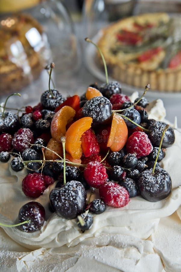 Meringhe del dolce con i frutti e le bacche Uva passa, ciliege, lamponi ed albicocche fotografie stock libere da diritti