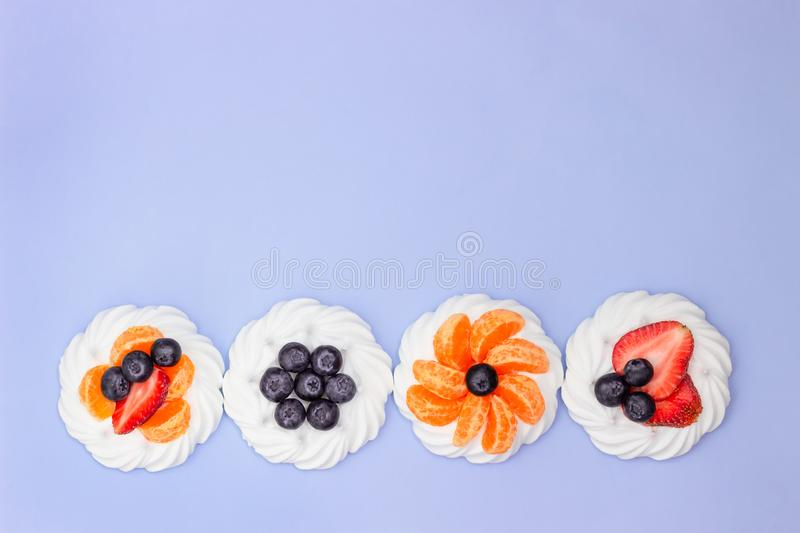 Meringue with blueberries, strawberries and tangerines on a lavender background. Minimal concept. Top view royalty free stock photography