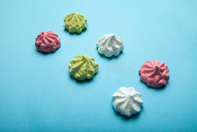Meringue multicolore délicieuse française sur un fond bleu photographie stock libre de droits