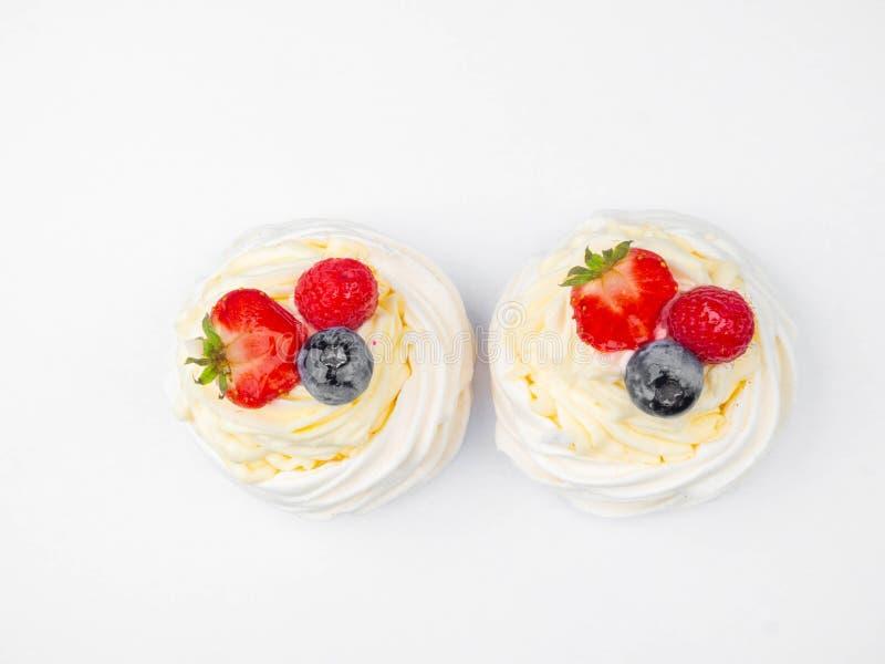 Meringue Pavlova with cream and fresh berries, strawberries, raspberries, blueberries isolated on white stock images