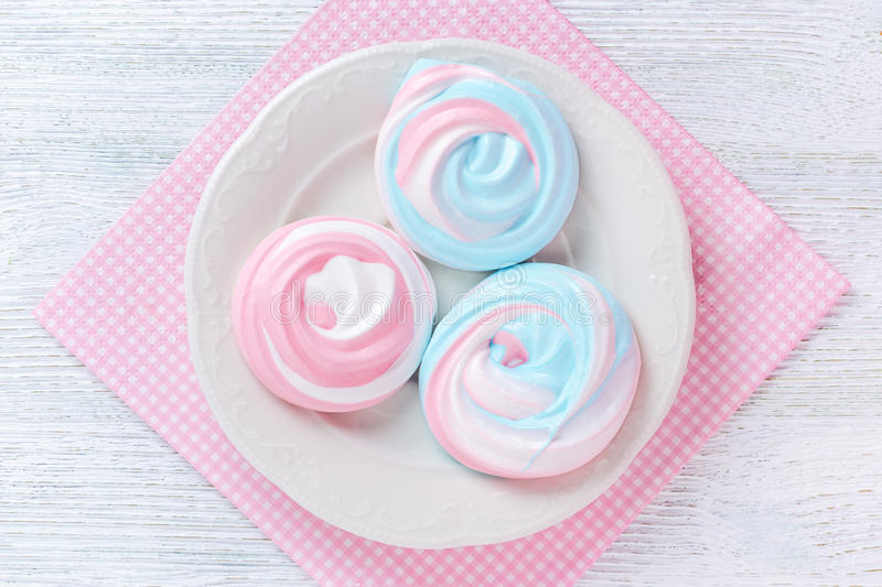 Meringues in pastel colors with abstract pattern on a plate and a pink serviette royalty free stock photo