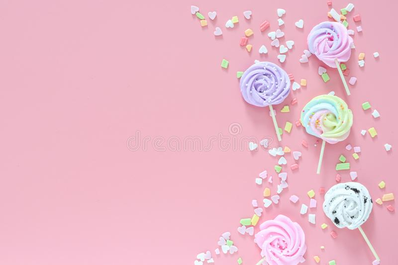 Meringues in pastel colors and scattered colorful on pink background. Meringues in pastel colors nd skattered colorful on pink background, greeting card, copy royalty free stock photo