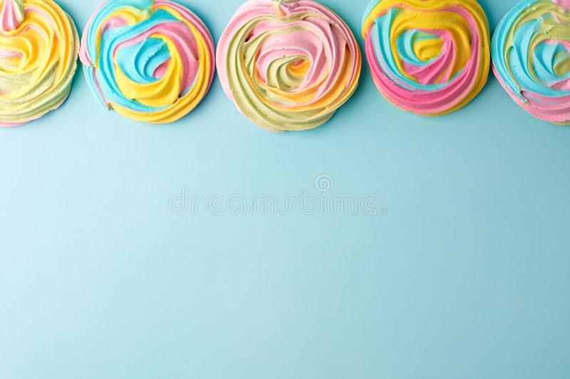 Meringues in unicorn rainbow pastel colors, frame and copy space on blue backgound, simple minimal.  royalty free stock image