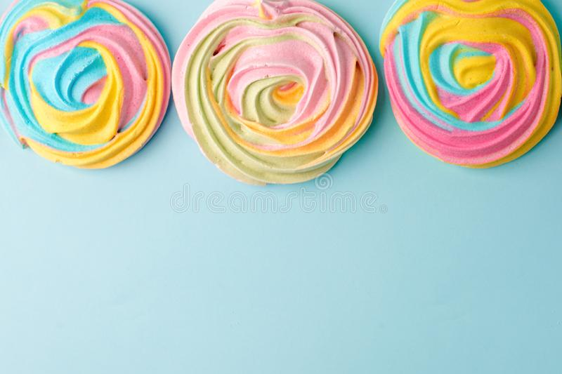 Meringues in unicorn rainbow pastel colors, frame and copy space on blue backgound, simple minimal.  royalty free stock photo