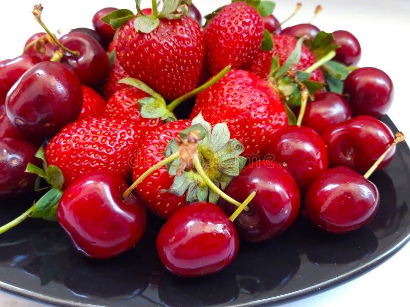 Merises et fraises de plat noir photo stock