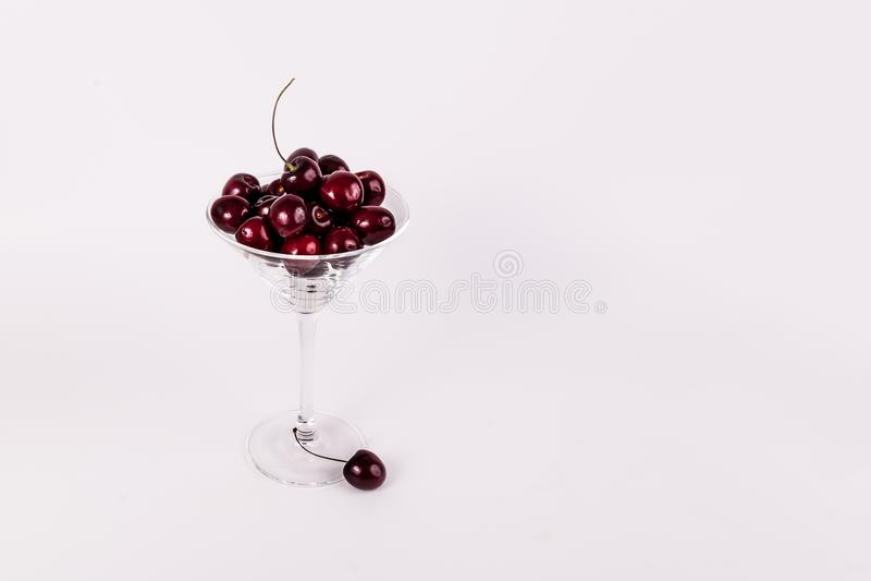 Merises organiques rouges en verre de martini sur le fond blanc photos libres de droits