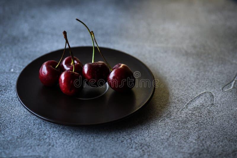 Merises rouges d'un plat noir sur une surface foncée photos libres de droits