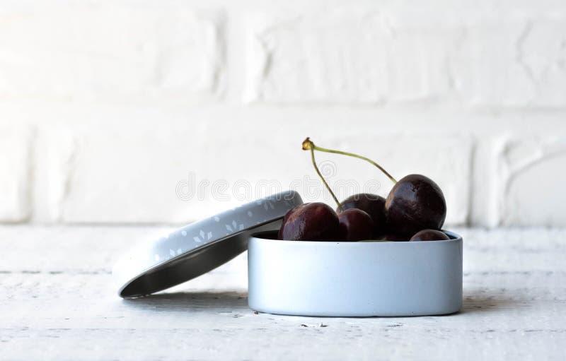 Merisiers dans le boîtier blanc sur le fond blanc en bois Savoureux, sain, baie d'été Cerises rouges Fermez-vous vers le haut de  photo stock