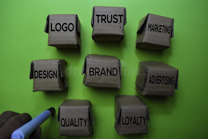 Merk, Ontwerp, Embleem, Vertrouwen, Marketing, Reclame, Loyaliteit, Kwaliteitstekst op vakje op groen bureau wordt geïsoleerd dat royalty-vrije stock fotografie