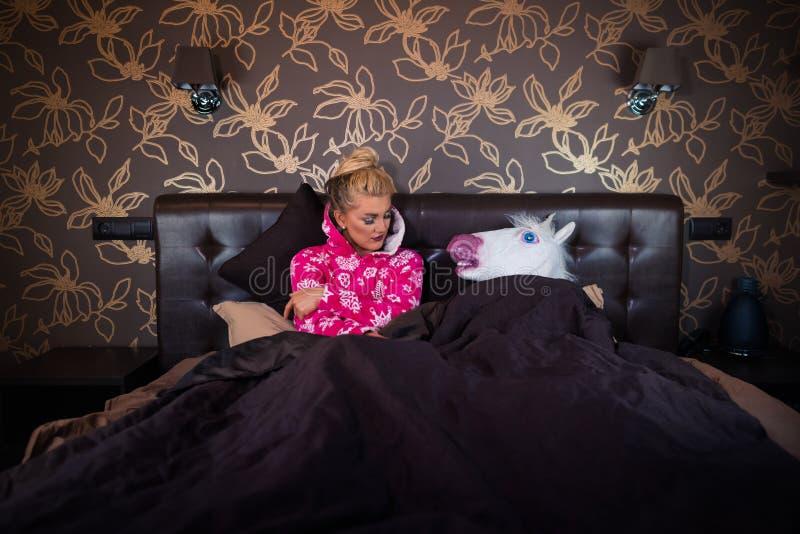 Merkwürdiger Mann in der Einhornmaske schlafend mit Mädchen lizenzfreie stockfotos