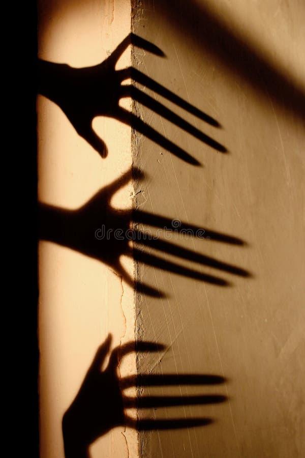 Merkw?rdiger Schatten auf der Wand Schrecklicher Schatten entziehen Sie Hintergrund Schwarzer Schatten einer gro?en Hand auf der  lizenzfreie stockfotos