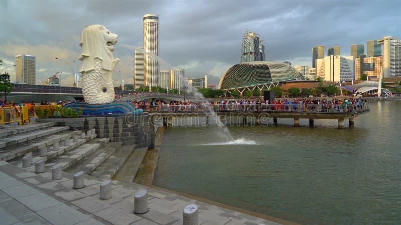 Merlion e molti turisti con le costruzioni del grattacielo nella città di Singapore ed in distretto finanziario al tramonto immagine stock