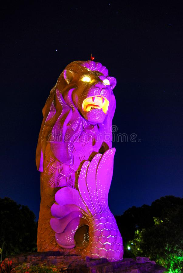 Merlion, lit up, mascot of Singapore, a mythical creature with a lion`s head and fish body, Sentosa, Singapore royalty free illustration