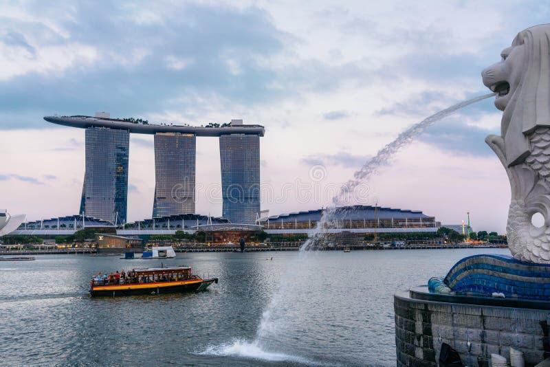 Merlion statyspringbrunn mot och Singapore stadshorisont på solnedgången royaltyfria bilder