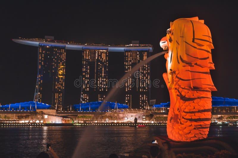 Merlionen med tigerband som förbiser Marina Bay Sands under Singapore iLight 2019 arkivbild
