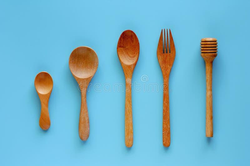 Merlo acquaiolo di legno del cucchiaio, della forchetta e del miele su fondo blu fotografia stock