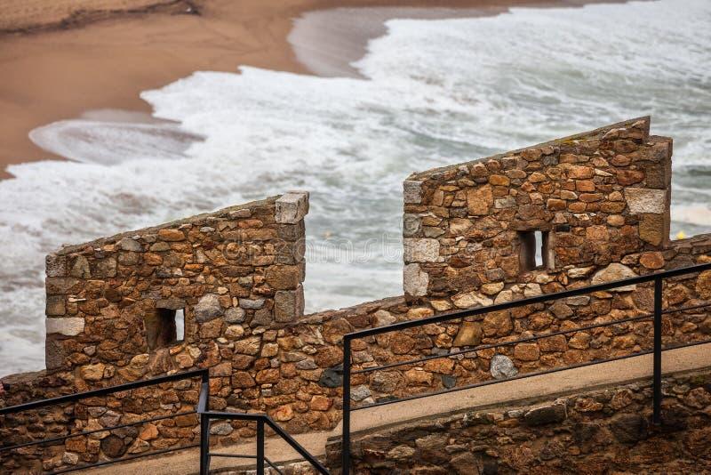 Merlo difensivo della parete di pietra dal mare fotografia stock