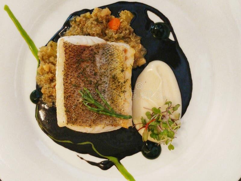 Merluches avec le quinoa avec l'encre de calmar photo stock