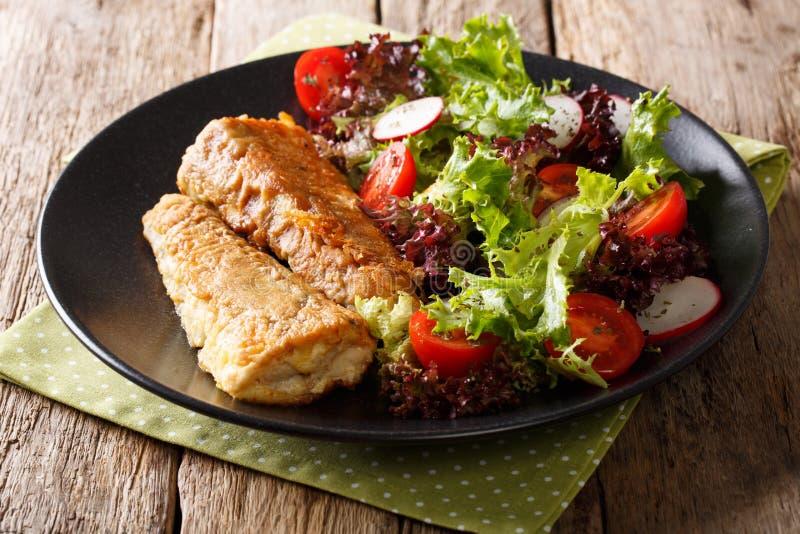 Merluches frites délicieuses avec le plan rapproché de salade de légume frais sur ventres image stock