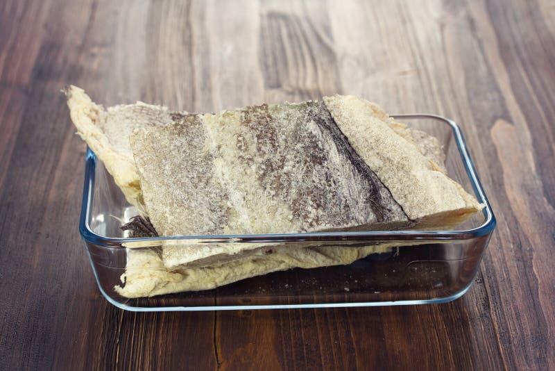 Merluzzo asciutto crudo salato sul piatto fotografia stock