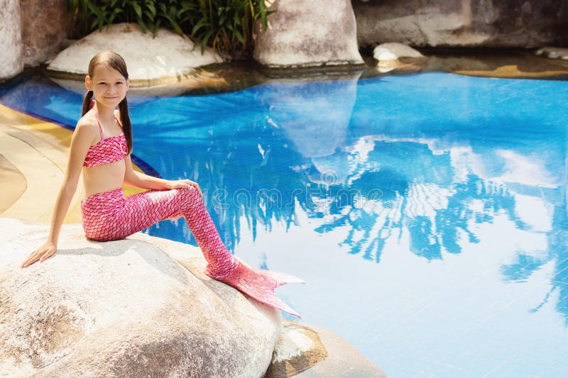 Mermaid girl with pink tail on rock at poolside stock photo