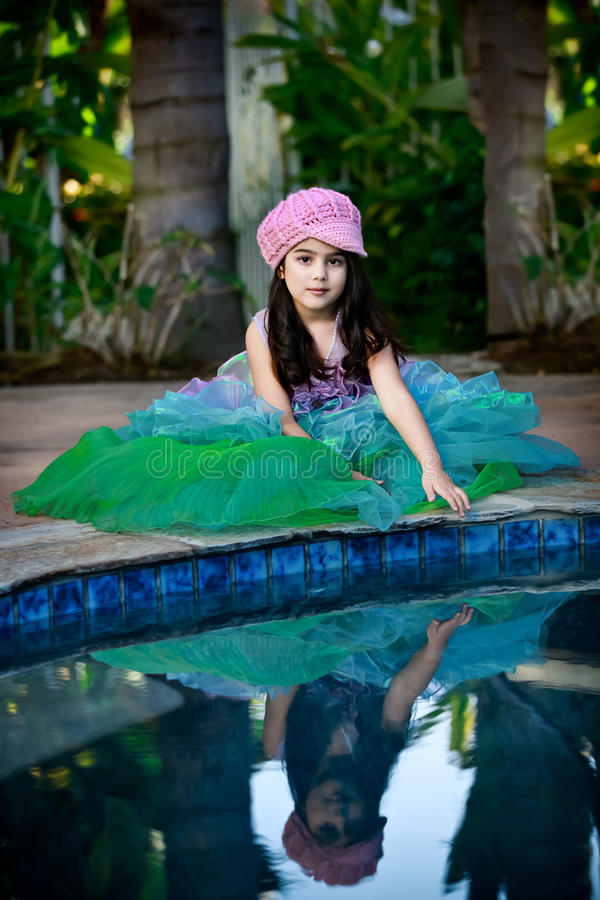 Mermaid by the pool. Little girl dressed in mermaid costume posing by the pool royalty free stock photos
