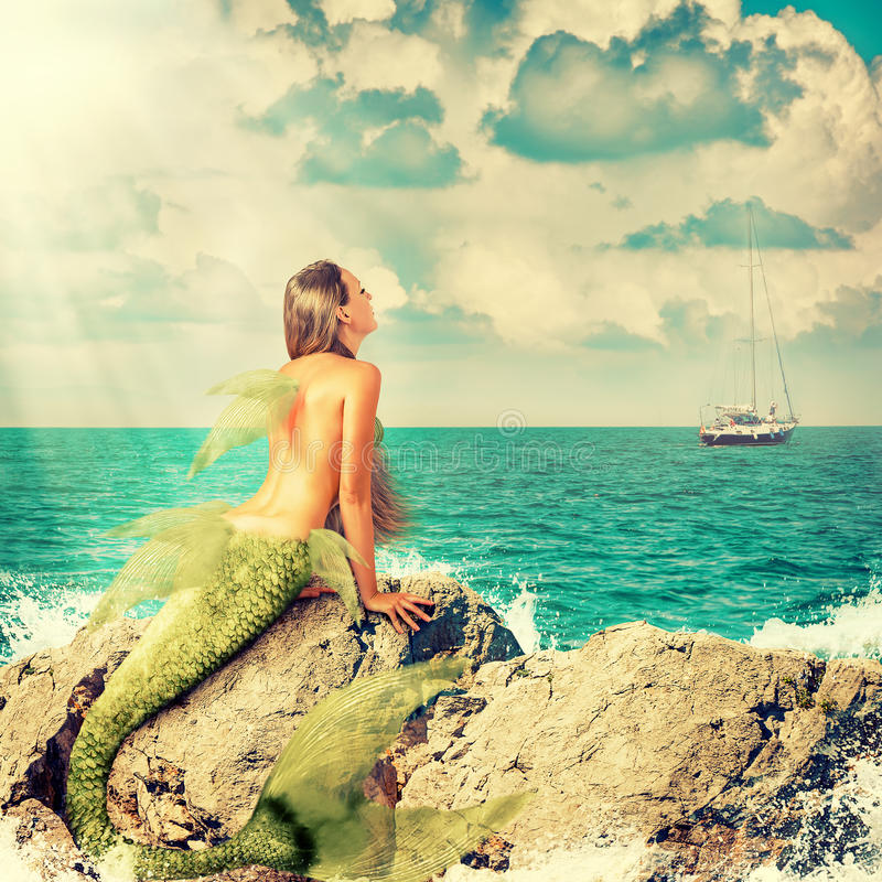Mermaid sitting on rocks. Beautiful Mermaid with fish tail sitting on rocks and looks at a ship on the horizon royalty free stock images