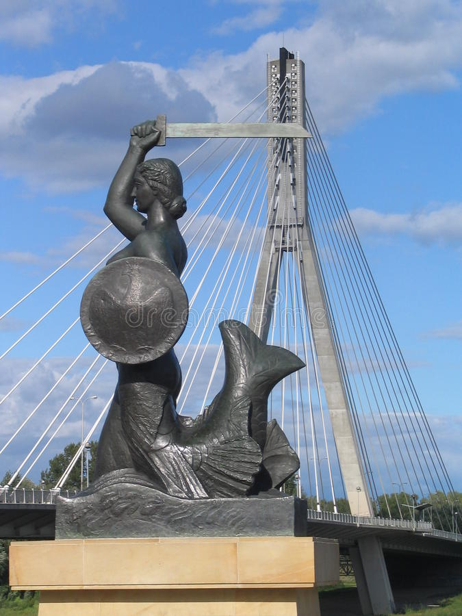 Mermaid and Swietokrzyski bridge in Warsaw, Poland. The monument of Syrenka (Mermaid) with a shield and a sword – a symbol of Warsaw (Poland) and the royalty free stock photo