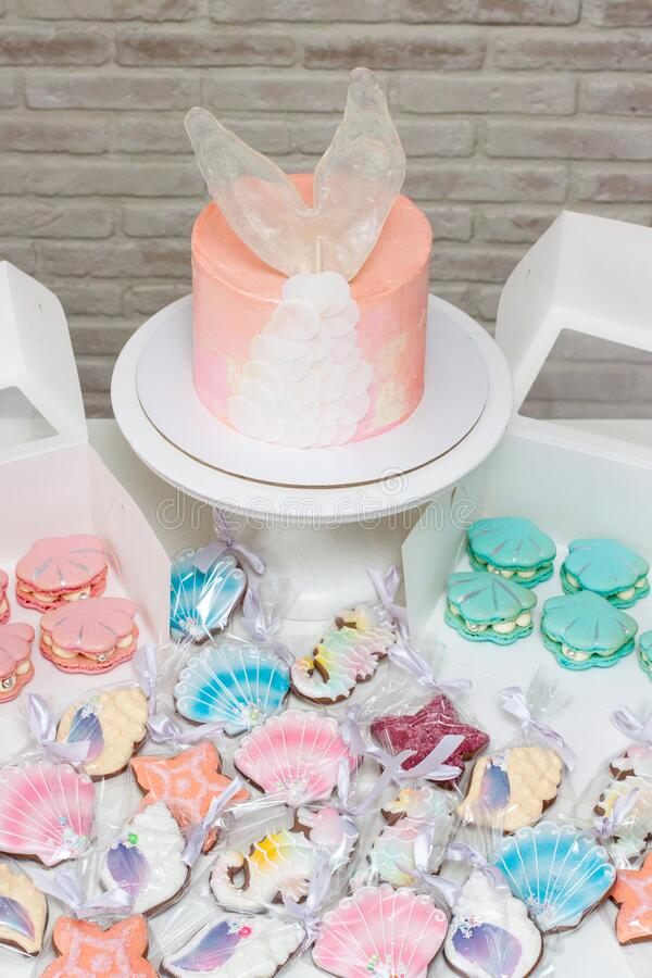Mermaid theme candy bar with pink cake with fish tail, french macaroons, soft pastel pink, peach and turquoise seashells biscuits stock photos