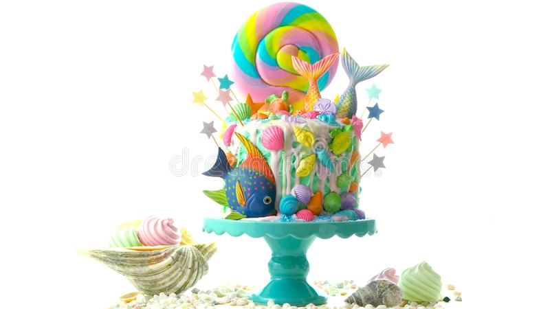 Mermaid theme candyland cake with glitter tails, shells and sea creatures. Mermaid theme candyland cake with colorful glitter tails, shells and sea creatures royalty free stock photos