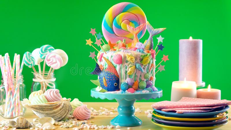 Mermaid theme candyland cake with glitter tails, shells and sea creatures. Mermaid theme candyland cake with colorful glitter tails, shells and sea creatures stock images