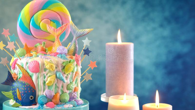 Mermaid theme candyland cake with glitter tails, shells and sea creatures. royalty free stock photo