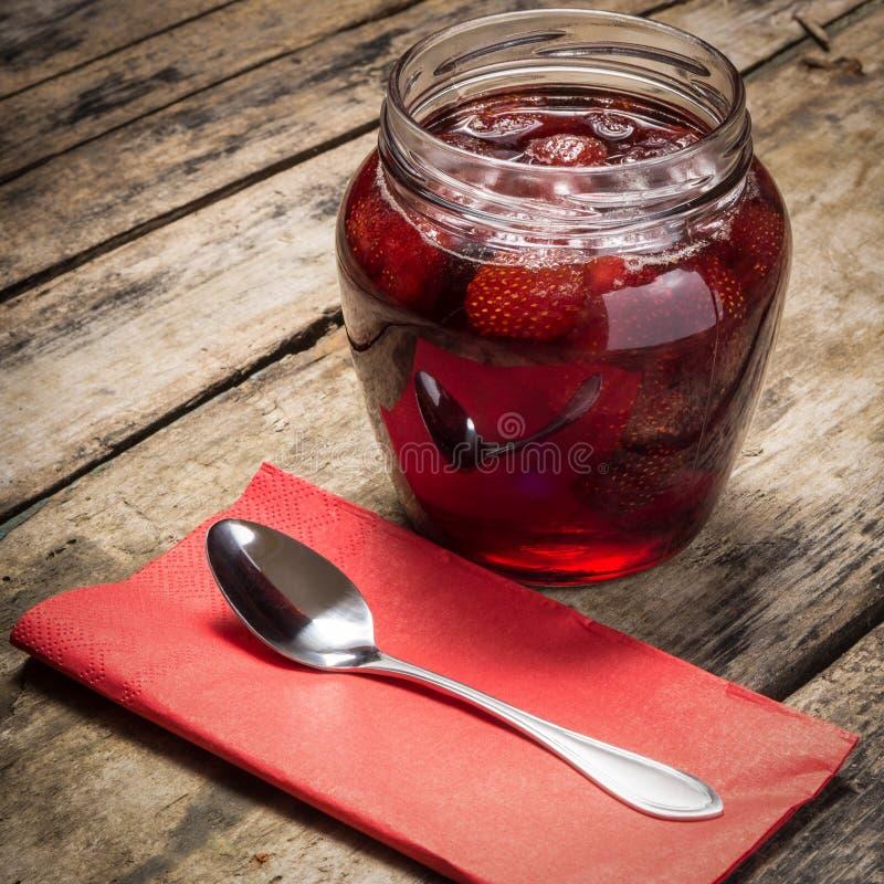 Mermelada de fresa con la cuchara servida en el fondo de madera imágenes de archivo libres de regalías