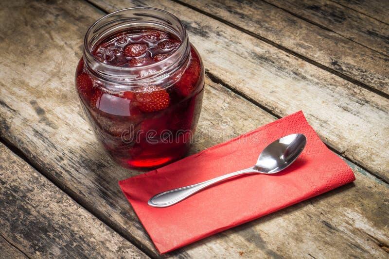 Mermelada de fresa con la cuchara servida en el fondo de madera fotografía de archivo libre de regalías