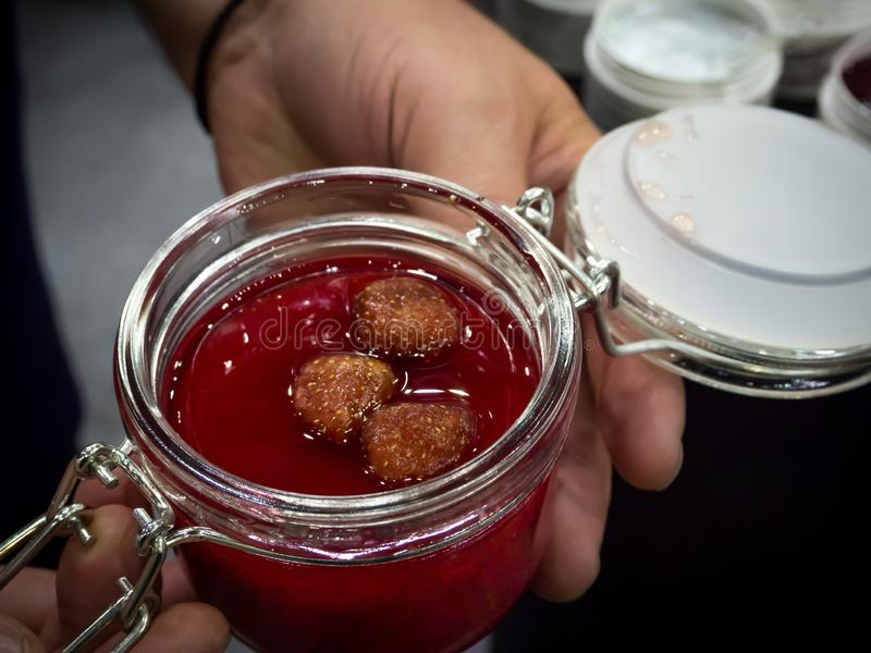 Mermelada de fresa en un tarro abierto Manos que celebran un tarro de mermelada de fresa foto de archivo libre de regalías