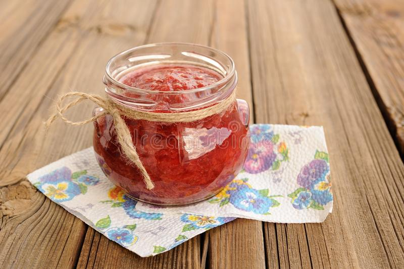 Mermelada de fresa hecha en casa en tarro de cristal abierto con hempstring en el pap imagen de archivo libre de regalías
