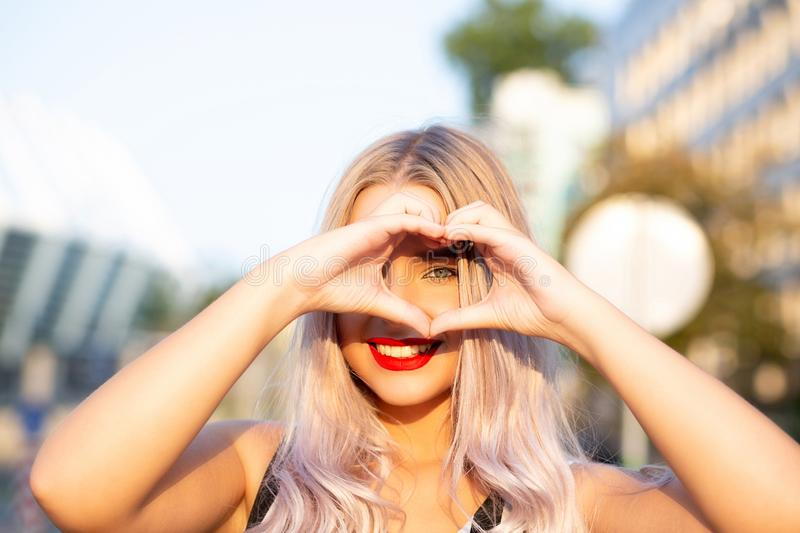 Merry blonde woman with red lips making heart sign with her fingers at the street stock image
