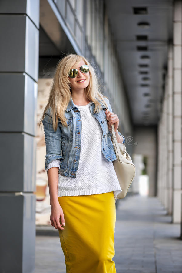 Merry cheerful caucasian girl. With long blond hair in denim jacket, a white sweater, a yellow skirt and white backpack with sun glasses go through the city and royalty free stock images